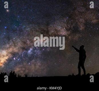 Die Silhouette eines Mannes, der ständigen und verweist auf die Milchstraße Hintergrund - Stockfoto