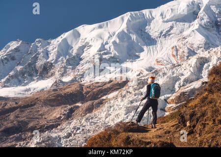 Stehende junge Frau mit Rucksack auf dem Berg und Blick auf die Berge und den Gletscher bei Sonnenuntergang. Landschaft - Stockfoto