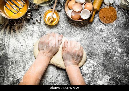 Teig Hintergrund. Frau knetet Teig mit verschiedenen Zutaten auf den Tisch. Auf rustikalen Hintergrund. - Stockfoto