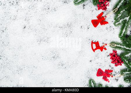 Weihnachten Hintergrund mit Schneeflocken, weißer Schnee, Spielzeug, Süßigkeiten, Weihnachtsbaum, Zweige und neues Jahr Dekor. Winterurlaub frame
