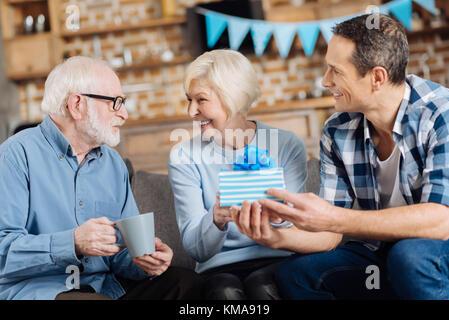 Glücklicher Mann seine Mutter mit Geburtstag gratulieren. - Stockfoto
