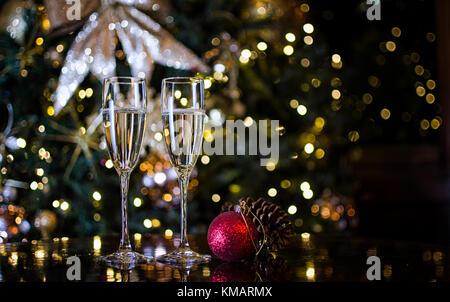 Zwei Sektgläser von Weihnachtsschmuck umgeben - Stockfoto
