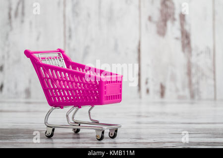 Miniatur purple Spielzeug Warenkorb auf weißem Holz- Hintergrund - Stockfoto