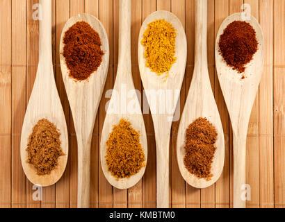 Haufen von gemahlenen Zimt, Paprika, Curry, Muskatnuss, Pfeffer auf holzlöffel in einer Reihe - Stockfoto