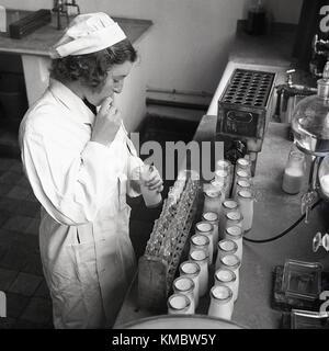 1950, historische, weibliche Labortechniker, die Milch aus der Flasche mit Strohhalm zu Reagenzglas Proben für die - Stockfoto