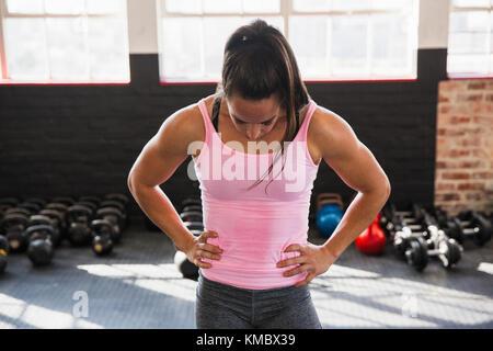Müde, muskulöse junge Frau mit Händen auf den Hüften ruht in der Turnhalle - Stockfoto