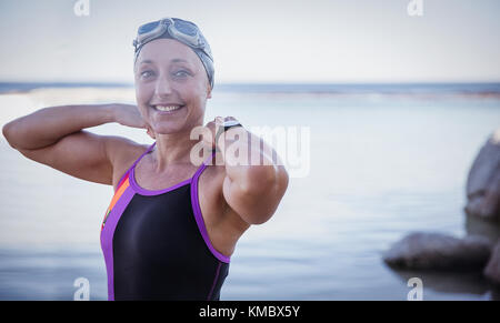 Portrait lächelnd weibliche Open water Schwimmer einstellen Badeanzug in Ocean - Stockfoto