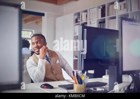 Lächelnd Geschäftsmann am Computer in die Arbeit im Büro - Stockfoto