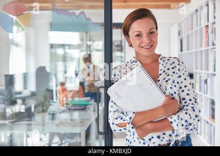 Portrait zuversichtlich Geschäftsfrau mit Notebook im Büro - Stockfoto
