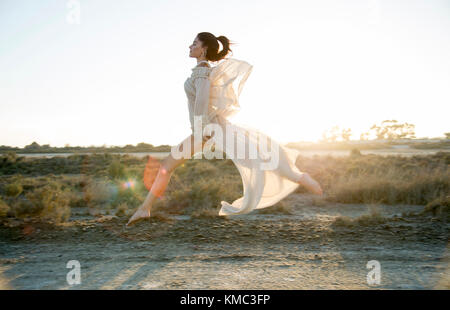Mädchen in das Feld bei Sonnenuntergang springen trägt ein weißes Kleid - Stockfoto