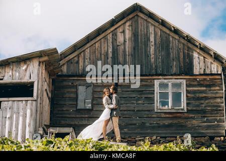 Brautpaar stand, lächeln und Hug während der Flitterwochen auf dem Hintergrund der alten Holzhütte. - Stockfoto