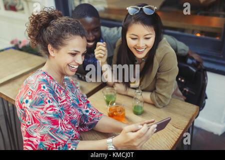 Junge Frauen Freunde mittels Smart Phone auf Sidewalk Cafe - Stockfoto