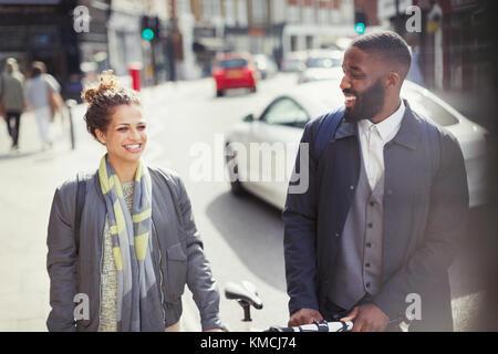 Lächelndes Paar pendeln mit Fahrrad auf sonnigen Urban Street - Stockfoto