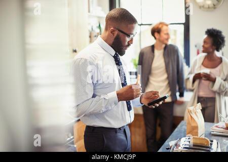 Geschäftsmann essen Frühstück und texting mit Smart Phone in der Küche - Stockfoto