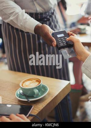 Kunden Bezahlung Kellner mit der Credit card reader im Cafe Tabelle - Stockfoto