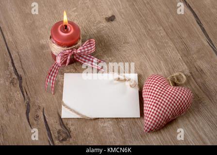 Eine leere Karte mit brennenden Kerzen und einem ausgestopften Baumwolle Herz auf Holz - Stockfoto