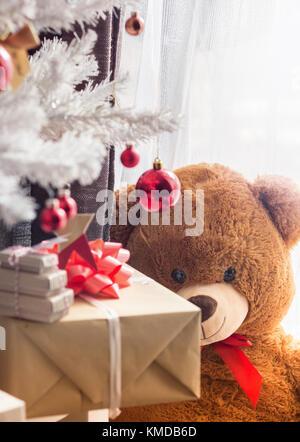 Big Teddy Bär am Fenster, Standortwahl hinter Weihnachtsbaum und Geschenke - Stockfoto