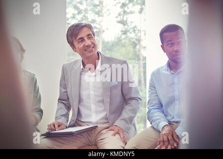 Lächelnde Menschen hören in der Gruppe Therapie Sitzung - Stockfoto