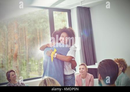 Mann und Frau umarmen in Gruppe Therapie Sitzung - Stockfoto