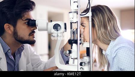 Aufmerksame optometrist Prüfung der weiblichen Patienten auf spaltlampe - Stockfoto