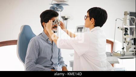 Frau tut Auge Test mit Optometriker in Augen Klinik - Stockfoto