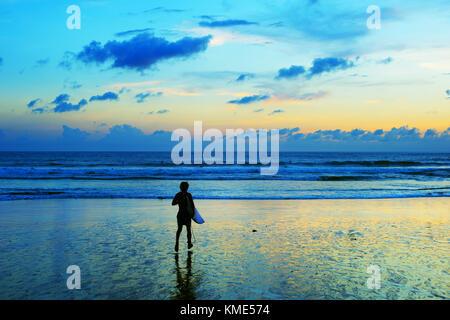 Surfer schnell zu Surfen im Meer bei Sonnenuntergang. Bsli Island, Indonesien - Stockfoto