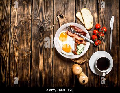 Frisches Frühstück mit einer Tasse Kaffee, gebratene Beck mit Eiern und Tomaten. Auf einem Holztisch. Stockfoto