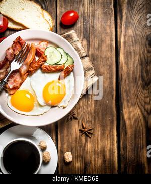 Frisches Frühstück mit einer Tasse Kaffee, gebratenen Speck mit Eiern und Tomaten. Auf einem Holztisch. Stockfoto