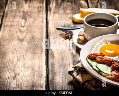 Frisches Frühstück. Tasse Kaffee, gebratenen Speck mit Eiern und geräucherte Wurst. auf Holz- Hintergrund. Stockfoto