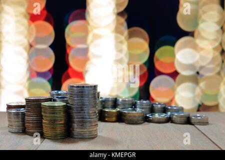 Münze Stapel Stapel auf dem Holztisch und Hintergrund des Lichts bokeh. Innovative Business speichern Konzept. - Stockfoto