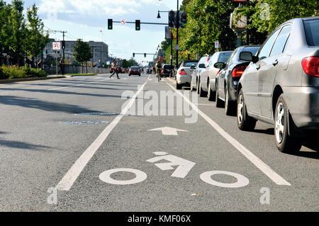 Radweg in Stadt Straße. Radfahrer Symbol auf Pflaster gemalt, Biker pendeln, Autos auf dem Parkplatz Gassen, Ampel, - Stockfoto