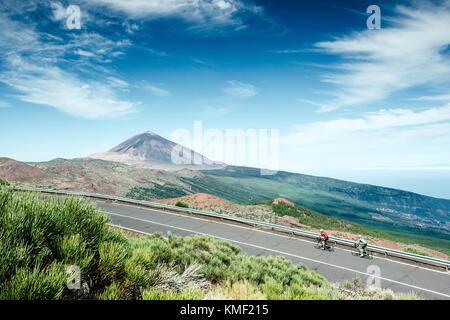 Zwei Radfahrer radeln auf Mountain Road mit Teide im Hintergrund Mount, Nationalpark Teide, Teneriffa, Kanarische - Stockfoto