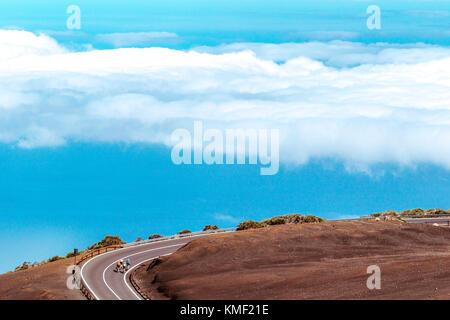 Radfahrer radeln auf kurvigen Bergstraße über den Wolken, Nationalpark Teide, Teneriffa, Kanarische Inseln, Spanien - Stockfoto