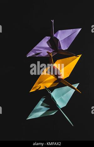 Krane origami aus Papier in verschiedenen Farben. Krane sind in Origami Technik auf einem dunklen Hintergrund. Krane - Stockfoto