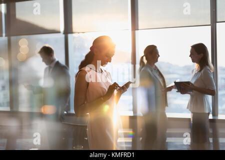 Geschäftsfrau SMS mit Handy im sonnigen Konferenzraum - Stockfoto