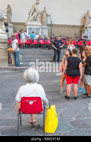 Eine Frau in einem roten Stuhl für einen Besuch Orchester zu spielen zu beginnen, an der Piazza della Signoria, - Stockfoto