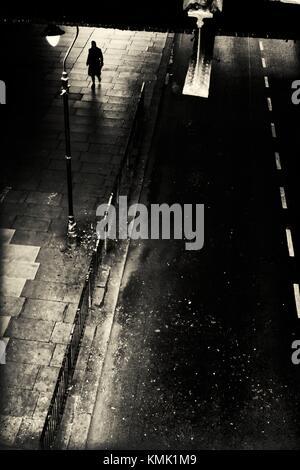 Silhouette der eine nicht erkennbare Mann auf der Straße unter einer Brücke. Waterloo Bridge, London, England, Großbritannien - Stockfoto