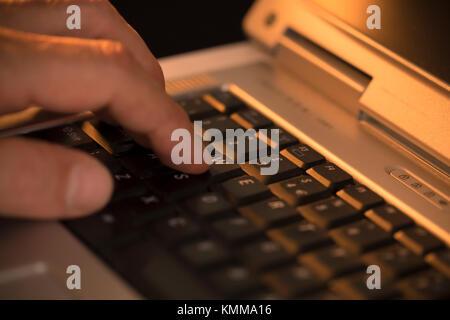 Mann durch Drücken einer Taste auf einem Laptop Tastatur - Stockfoto