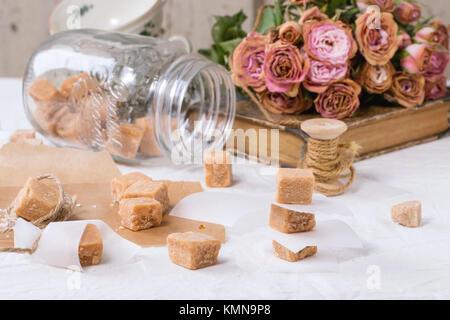 Fudge Bonbons und Karamell, auf Backpapier in Glas, diente über weiße Tischdecke mit Blumenstrauß aus trockenen - Stockfoto