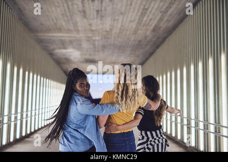 Rearview einer Gruppe junger Freundinnen Spaß beim Gehen Arm in Arm zusammen auf einem Gehweg in die Stadt bei Nacht - Stockfoto