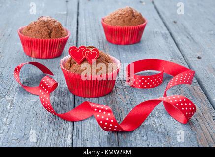 Chocolate Muffins in rot Pappbecher mit Herzen und ein Band eingerichtet - Stockfoto