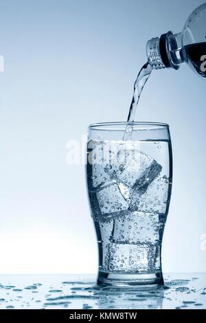 Kalten gereinigtes Wasser in das Glas mit Luftblasen und Reflexion auf dem nassen Hintergrund - Stockfoto