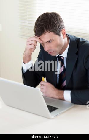 Konzentrierte Geschäftsmann Arbeiten am Laptop in seinem Büro - Stockfoto