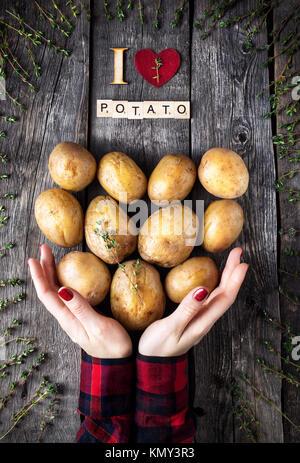 Frau Kartoffel Holding mit Thymian auf rustikalen Holzmöbeln Hintergrund aus der Sicht von oben - Stockfoto