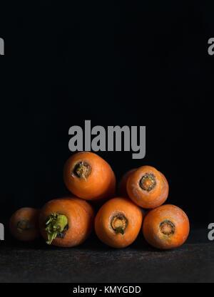 Karotten auf der schwarzen Oberfläche auf schwarzem Hintergrund - Stockfoto