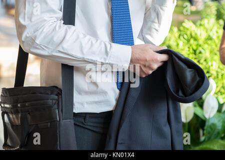 Unternehmer nehmen Anzug aus und sprechen mit Freundin nach der Arbeit im Korridor Bürogebäude, nach der Arbeit - Stockfoto