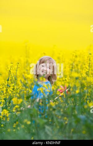 Junge mit langen blonden Haaren mit Windrad in Raps Feld - Stockfoto