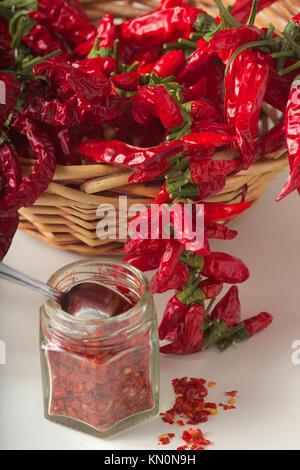 Scharfe rote Pfeffer im Glas, mit gesunden getrocknete Paprika in den Korb - Stockfoto