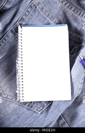 Ein Notizbuch auf eine Jeans-Hose. - Stockfoto