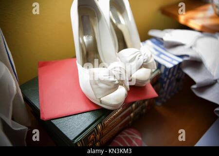 Unordentliches Zimmer mit Braut Schuhe auf dem Stapel Bücher. - Stockfoto
